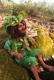 Figura fatta a mano della bambola leggiadramente che si siede sulla pietra in terreno boscoso Fotografia Stock