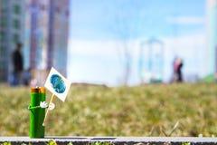 A figura humanizada feita da bateria do AA realiza no cartaz das mãos com o o símbolo do globo do Dia da Terra Conceito do feriad Foto de Stock Royalty Free