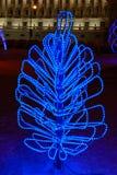 Figura illuminata dell'albero di Natale dalle ghirlande sulle luci nei precedenti alla notte Immagine Stock