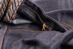 A figura minúscula abre o zíper, fecha calças de brim do zíper Fotos de Stock