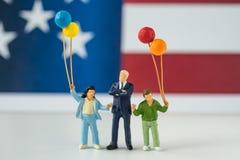 Figura miniatura americana feliz familia que sostiene los globos con Uni Foto de archivo libre de regalías