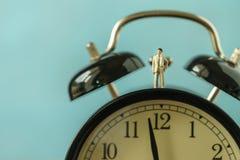 Figura miniatura del hombre de negocios que se coloca en el despertador como negocio Imágenes de archivo libres de regalías