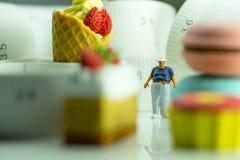 Figura miniatura di un uomo obeso e di un alimento non sano Immagine Stock