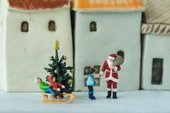 Figura miniatura donante de Papá Noel presente a los niños felices como Fotografía de archivo libre de regalías