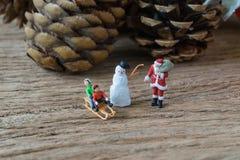 Figura miniatura donante de Papá Noel presente a los niños felices como Imagenes de archivo