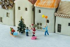 Figura miniatura donante de Papá Noel presente a los niños felices como Fotos de archivo libres de regalías