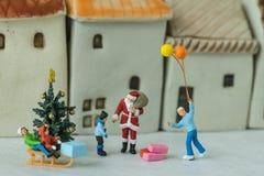 Figura miniatura donante de Papá Noel presente a los niños felices como Fotografía de archivo