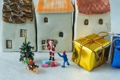 Figura miniatura donante de Papá Noel presente a los wi felices de los niños Imágenes de archivo libres de regalías