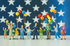 Figura miniatura familia americana feliz que sostiene el globo con los E.E.U.U. Imágenes de archivo libres de regalías