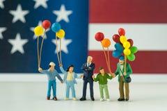 Figura miniatura, familia americana feliz que sostiene el globo con Uni Imágenes de archivo libres de regalías