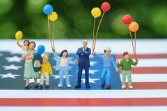 Figura miniatura, familia americana feliz que sostiene el globo con Uni Fotos de archivo