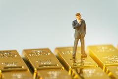 Figura miniatura hombre de negocios que se coloca en ing brillante de los lingotes de oro fotos de archivo libres de regalías
