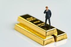 Figura miniatura hombre de negocios que se coloca y que piensa en el oro brillante imágenes de archivo libres de regalías