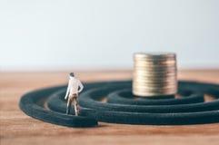 Figura miniatura hombres de negocios que dan une vuelta con las monedas de oro Foto de archivo libre de regalías