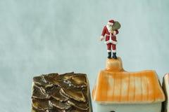 Figura miniatura Papá Noel que se coloca en la chimenea del tejado como christm Fotos de archivo libres de regalías