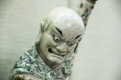 Figura oriental de la porcelana que mira abajo imagenes de archivo