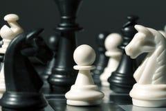 Figura pegno di scacchi sul bordo Il pegno bianco nel nero dipende la scacchiera fotografia stock