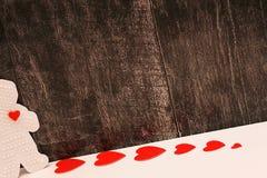 Figura plástica de un hombre con un corazón rojo Los corazones rojos de la cartulina se arreglan en fila Concepto de amor Fondo d fotos de archivo libres de regalías