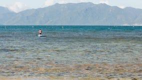 Figura posição do homem no paddleboard das fileiras dos joelhos no oceano video estoque