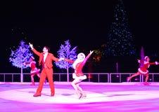 Figura profesional patinadores del hombre y de la mujer que se realizan en la Navidad en la demostración de hielo en área interna imagen de archivo