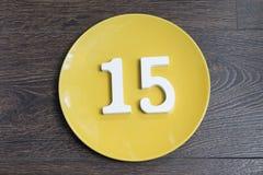 Figura quindici sul piatto giallo Immagini Stock Libere da Diritti