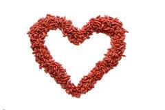 Figura roja del corazón hecha de muchas bayas secadas de Goji Muestra del corazón aislada Foto de archivo libre de regalías