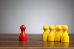 Figura rossa del pegno contro giallo unito, isolamento, confronto, Fotografia Stock