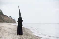 Figura sconosciuta in mantello nero con il fronte di specchio in spiaggia immagine stock