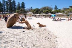 Figura scultura con il cane sulla spiaggia Fotografia Stock