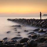 Figura solitaria soportes que miran hacia fuera al mar Imagen de archivo