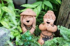 Figura sorridente scultura della ragazza dell'argilla tailandese del giardino immagine stock