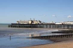Figura sulla spiaggia con il pilastro di Hastings Fotografie Stock Libere da Diritti
