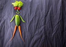 Figura umana fatta delle verdure su fondo di carta nero Perdita di peso e stile di vita sano Con spazio per testo immagini stock libere da diritti