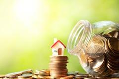 Figura vermelha da forma da casa na pilha e na pilha das moedas imagens de stock royalty free