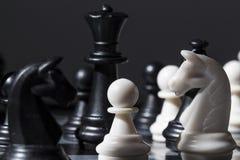 Figuras blancos y negros del ajedrez en el tablero de ajedrez Proceso del juego del jaque mate Foto de archivo libre de regalías