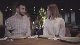 Figuras borradas do homem farpado e da mulher elegante que falam no fundo que senta-se no restaurante confortável moderno em vídeos de arquivo