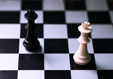 Figuras brancas e pretas da xadrez a bordo Posição do jogo de xadrez Rei preto e branco fotografia de stock royalty free