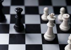 Figuras brancas e pretas da xadrez a bordo Posição do jogo de xadrez Rei preto e branco foto de stock