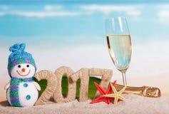 Figuras 2017, champanhe da garrafa e vidro, boneco de neve, estrela do mar contra o mar Fotografia de Stock Royalty Free