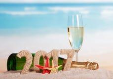 Figuras 2017, champanhe da garrafa e vidro, estrela do mar contra o mar Fotografia de Stock