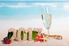 Figuras 2017, champanhe da garrafa e vidro, estrela do mar, presentes contra o mar Imagem de Stock Royalty Free