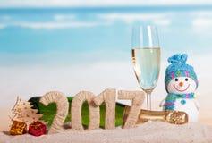 Figuras 2017, champanhe da garrafa, vidro, boneco de neve, árvore, presentes contra o mar Imagens de Stock Royalty Free