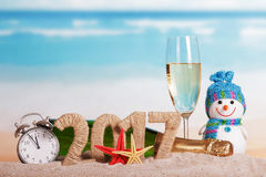 Figuras 2017, champanhe da garrafa, vidro, boneco de neve, despertador, contra o mar Imagens de Stock Royalty Free