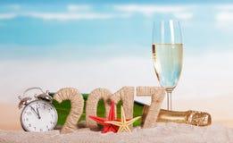 Figuras 2017, champanhe da garrafa, vidro, despertador, estrela do mar contra o mar Fotos de Stock