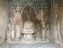 Figuras cinzeladas com a estátua de Sakyamuni na gruta Fotografia de Stock Royalty Free