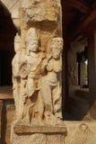 Figuras cinzeladas nas colunas sóbrios e quadradas do patamar da entrada do templo de Durga, Aihole, Bagalkot, Karnataka O Galaga Imagens de Stock Royalty Free