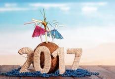Figuras coco 2017 e grânulos na tabela contra o mar Fotografia de Stock