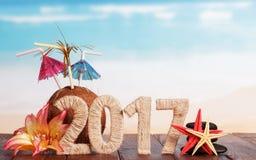Figuras coco 2017, estrela do mar e flores na tabela contra o mar Foto de Stock