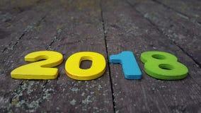 figuras coloreadas para formar el número 2018 en fondo de madera Imagen de archivo