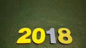 figuras coloreadas para formar el número 2018 en un fondo verde Imagen de archivo